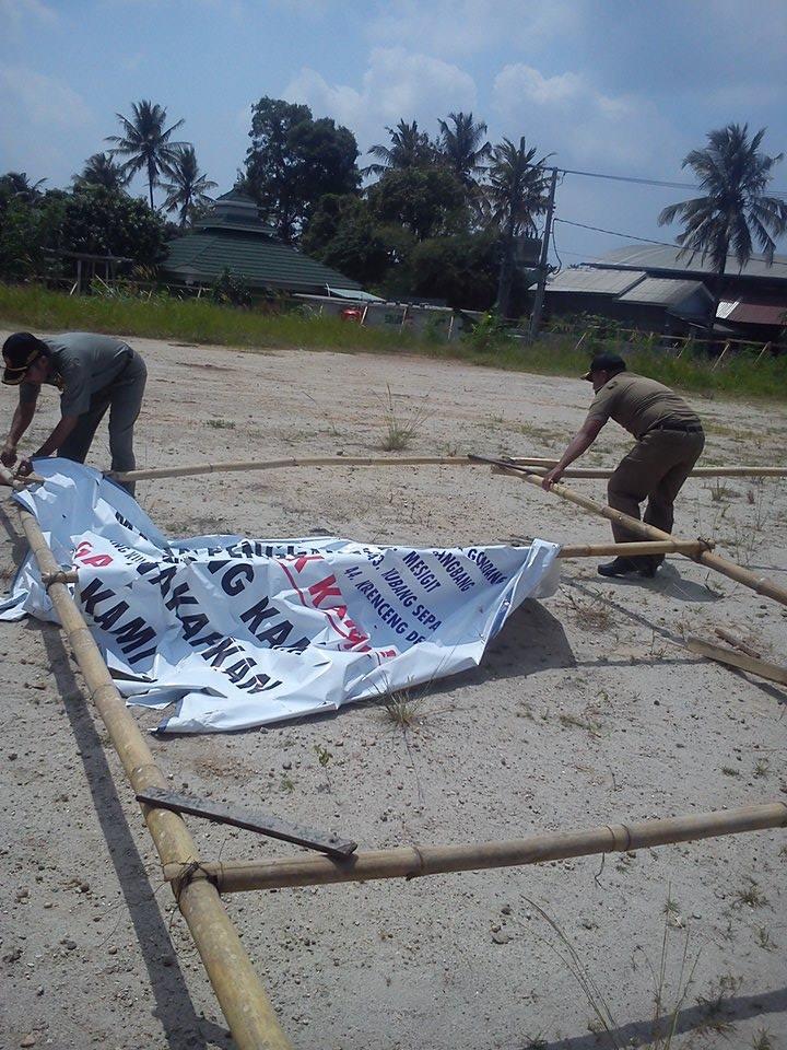 Pengelola yayasan makam balung  dibantu Satpol PP Kecamatan Citangkil mencabut spanduk penolakan Rusunawa oleh warga setempat