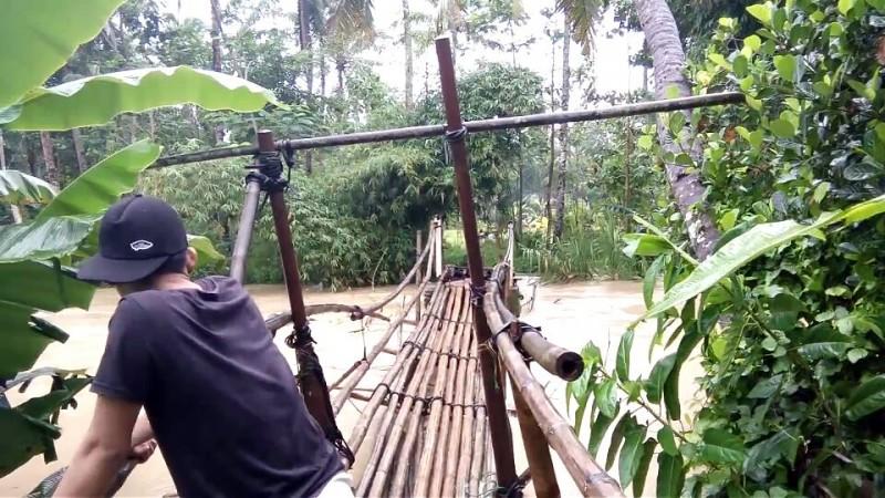 Seorang Warga Saat Hendak Melintas Di Jembatan Bambu Yang Rawan Ambruk. (Foto, BidikBanten)