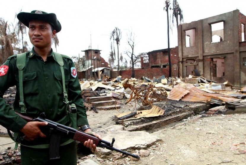 seorang-tentara-myanmar-tengah-berjaga-di-bangunan-yang-rusak